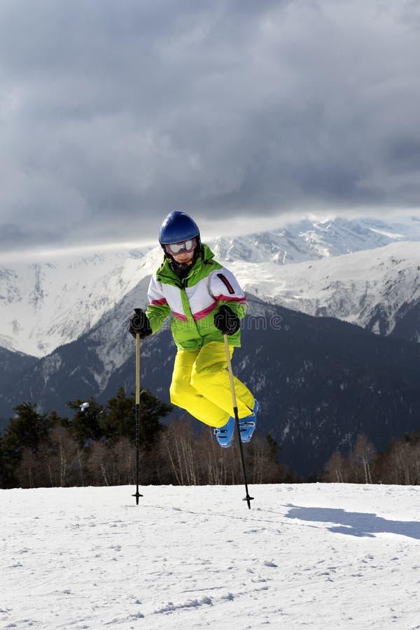 El esquiador joven salta con los polos de esquí en montañas y clou del invierno del sol foto de archivo