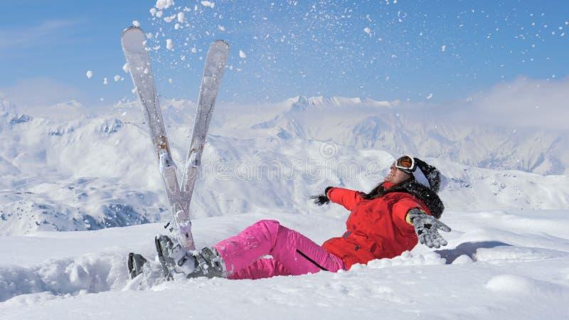 El esquiador lanza para arriba nieve en el aire, aumenta su pierna y cae en la nieve foto de archivo libre de regalías