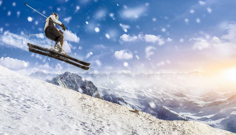 El esquiador salta cuesta abajo a través del aire en la puesta del sol en el ambiente hivernal imagen de archivo