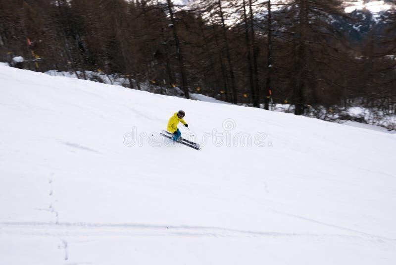 El esquiador va abajo en la cuesta de las montañas imagen de archivo