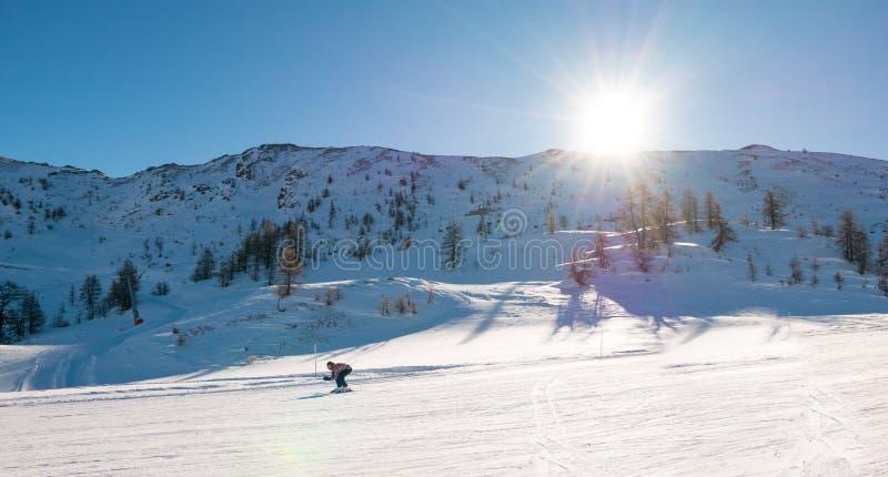 El esquiador va abajo en la pista nevosa del esquí fotos de archivo