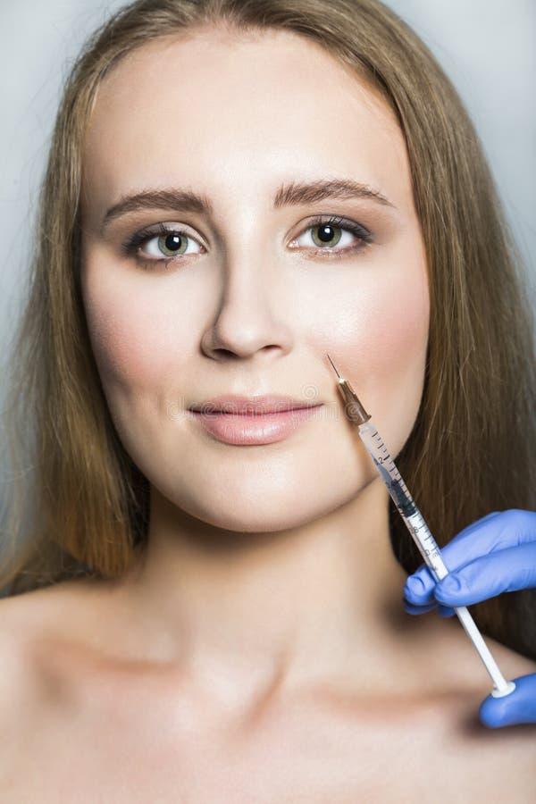 El estético del doctor hace inyecciones de la belleza de la cara al paciente femenino imagenes de archivo