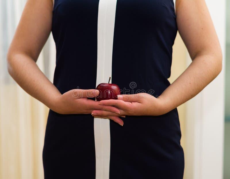 El estómago de la mujer del primer que lleva el vestido azul, sosteniendo la manzana entre las manos, concepto de los weightloss fotografía de archivo libre de regalías