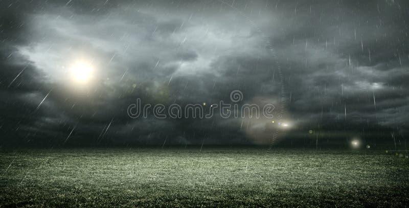 El estadio de fútbol imaginario con las nubes y la lluvia oscuras, representación 3d fotografía de archivo