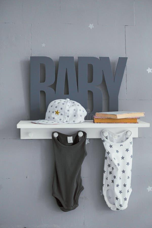 El estante de la ropa del ` s de los niños con gris pone letras al bebé foto de archivo libre de regalías