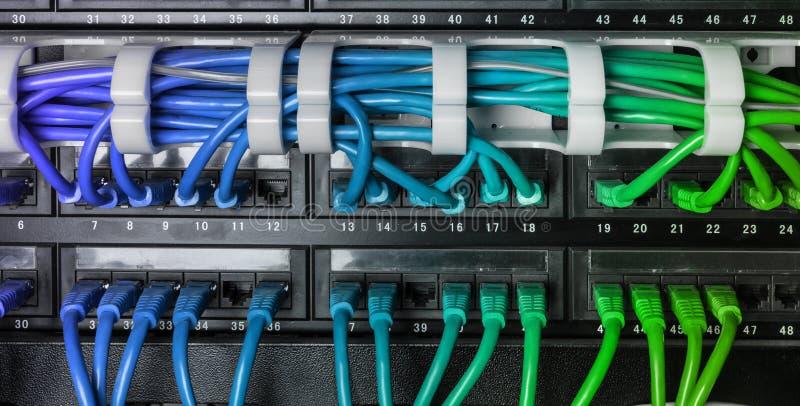 El estante del servidor con el cordón de remiendo azul de Internet telegrafía foto de archivo