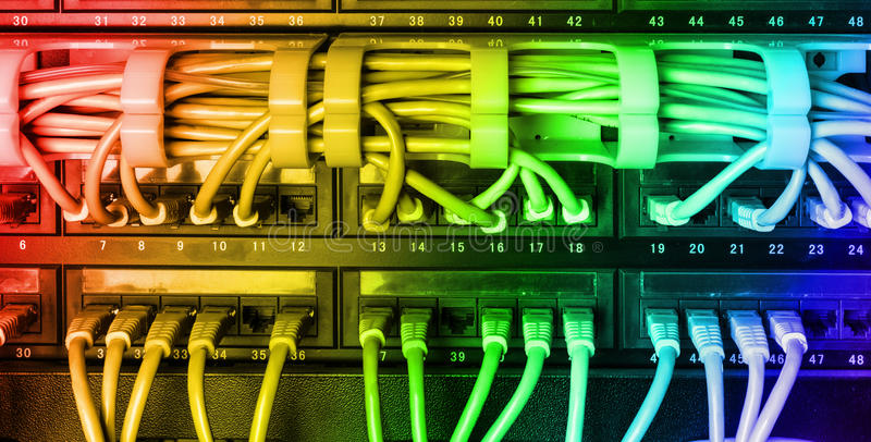 El estante del servidor con el cordón de remiendo de Internet del arco iris telegrafía fotos de archivo libres de regalías