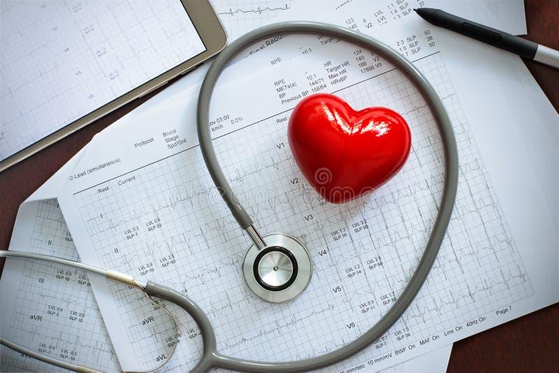 El estetoscopio con forma roja del corazón y el examen anual divulgan foto de archivo