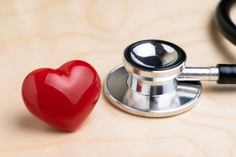 El estetoscopio del doctor con el corazón rojo del hockey shinny en la tabla de madera, la atención sanitaria, el examen médico o fotografía de archivo
