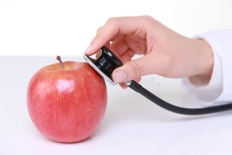 El estetoscopio del médico examina una manzana foto de archivo