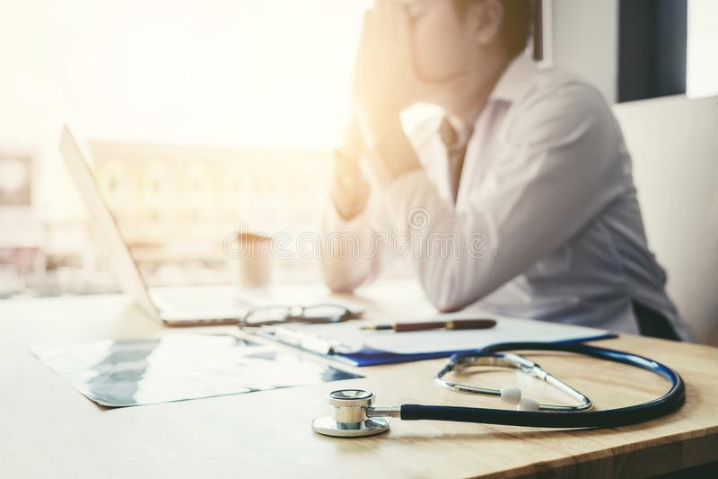 El estetoscopio y el doctor que se sientan con el ordenador portátil subrayan abou del dolor de cabeza imagen de archivo