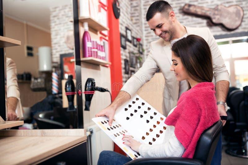 El estilista ayuda al cliente a elegir el tinte del color del pelo de palet fotos de archivo libres de regalías