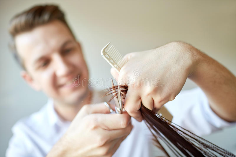 El estilista con las tijeras que cortan el pelo inclina en el salón imagenes de archivo