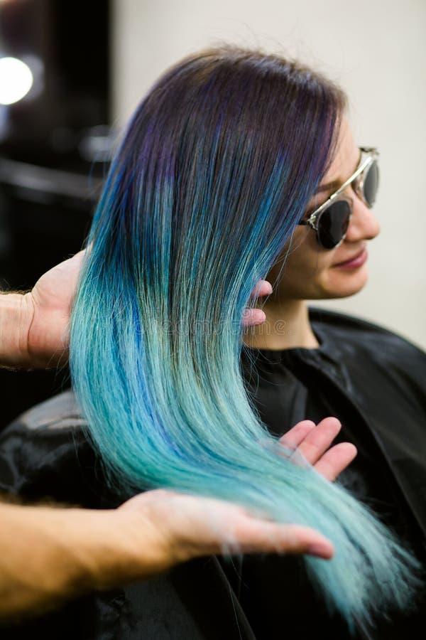 El estilista demuestra su trabajo con la muchacha hermosa Azul teñido corte de pelo del color del pelo del peluquero imagen de archivo libre de regalías