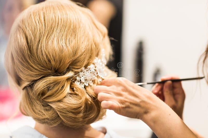El estilista hace a la novia antes de una boda foto de archivo