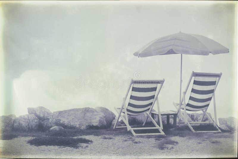 El estilo del vintage filtró imagen de dos sillas y paraguas vacíos de playa en la costa costa fotos de archivo libres de regalías