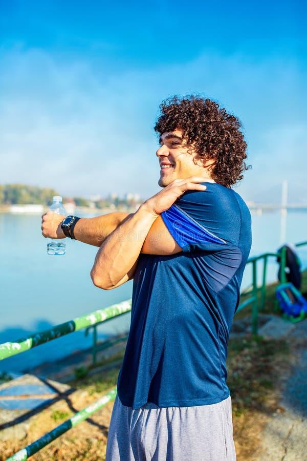 El estirar de funcionamiento - hombre de la aptitud que corre haciendo ejercicios en imagen de archivo libre de regalías