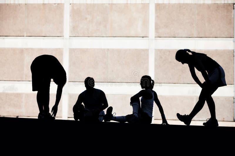 El estirar de los corredores de los hombres y de las mujeres. imagen de archivo libre de regalías