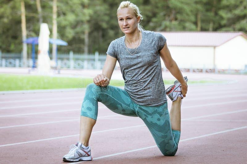 El estirar del ejercicio del atleta de sexo femenino fotografía de archivo libre de regalías