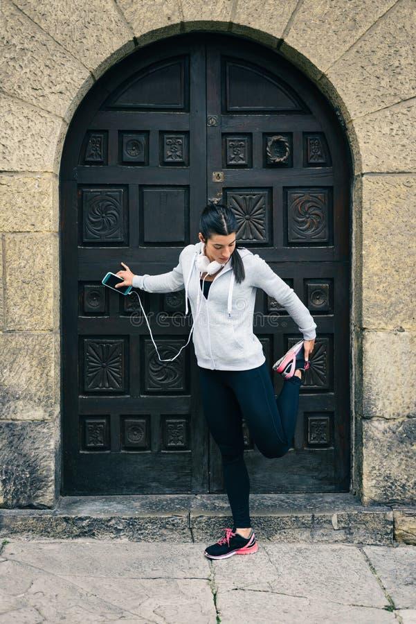 El estirar femenino del corredor del ajuste urbano imagen de archivo