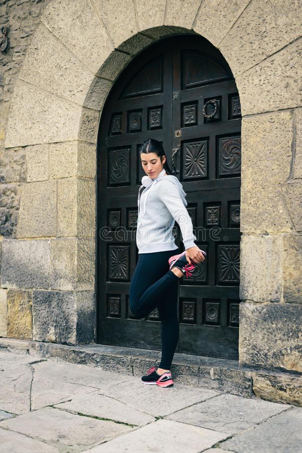 El estirar femenino del corredor del ajuste urbano imagen de archivo libre de regalías