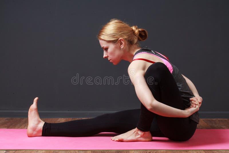 El estirar Mujer rubia joven que hace ejercicio de la yoga imagen de archivo