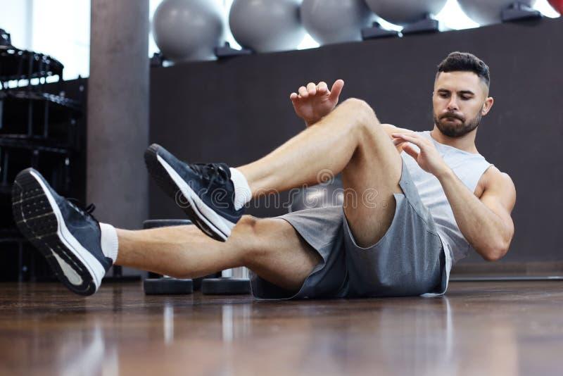 El estirar y calentamiento deportivos del hombre que hacen los ejercicios especiales para los músculos antes de trabajo su cuerpo imágenes de archivo libres de regalías