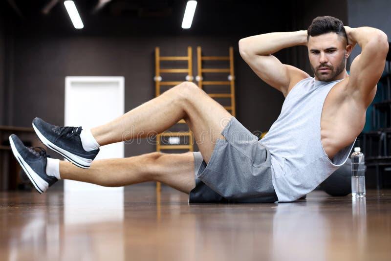 El estirar y calentamiento deportivos del hombre que hacen los ejercicios especiales para los músculos antes de trabajo su cuerpo imagenes de archivo