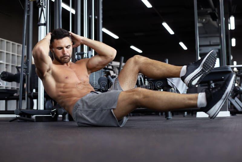 El estirar y calentamiento deportivos del hombre que hacen los ejercicios especiales para los músculos antes de trabajo su cuerpo foto de archivo libre de regalías
