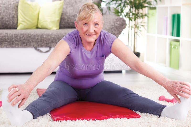 El estirar y ejercicio mayores de la mujer en casa fotografía de archivo