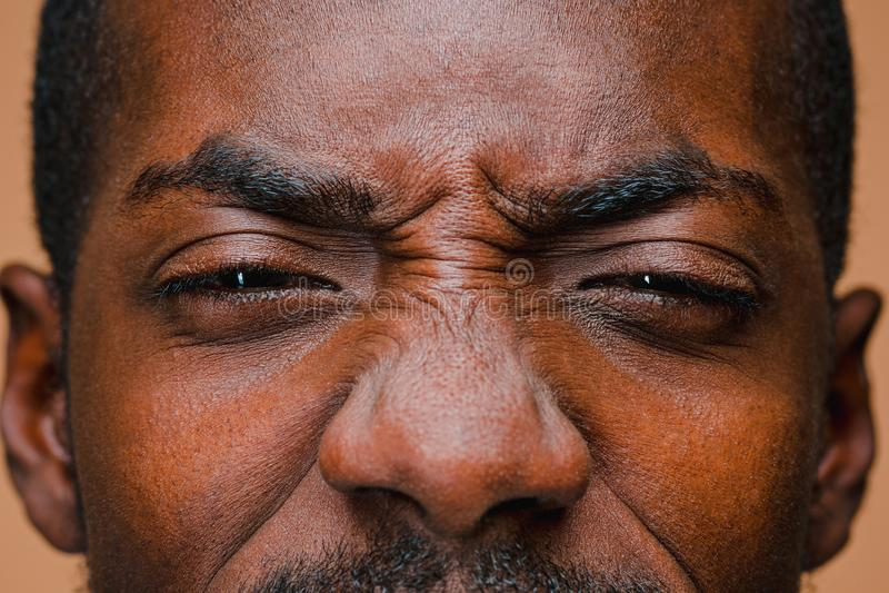 El estrabismo del hombre elegante afroamericano en la pared marrón del estudio imagen de archivo