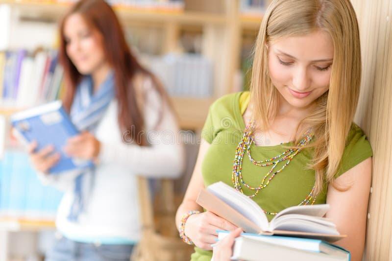 El estudiante adolescente leyó el libro en la biblioteca de la High School secundaria imagen de archivo
