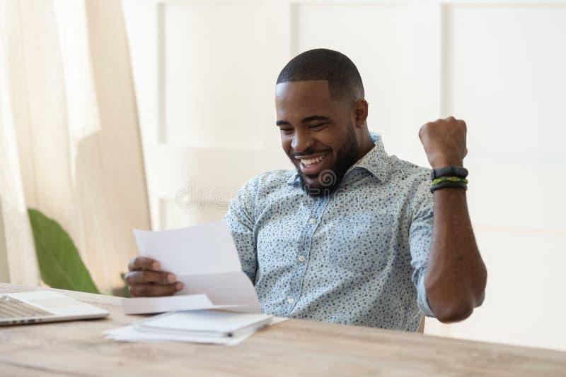 El estudiante africano emocionado del hombre de negocios leyó la letra feliz sobre buenas noticias imágenes de archivo libres de regalías