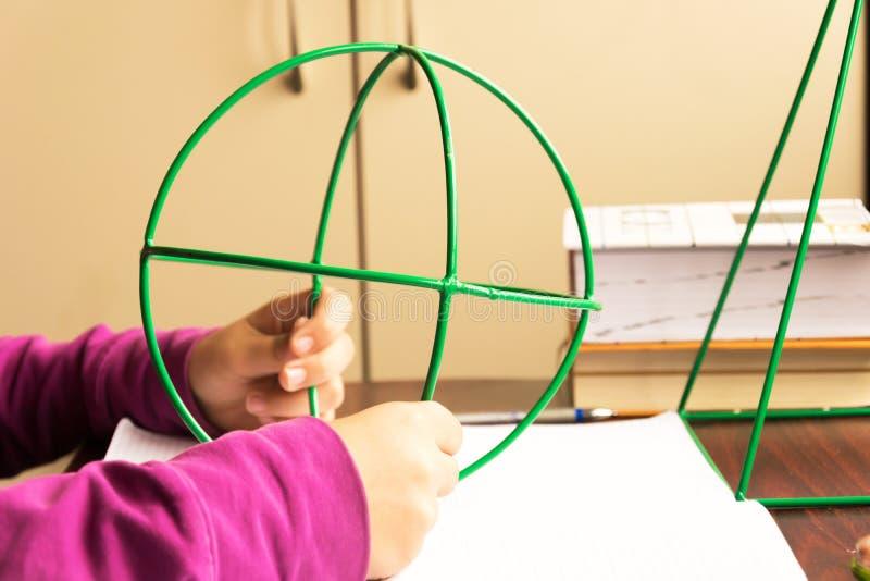 El estudiante aprende matemáticas usando esfera del wireframe imagenes de archivo