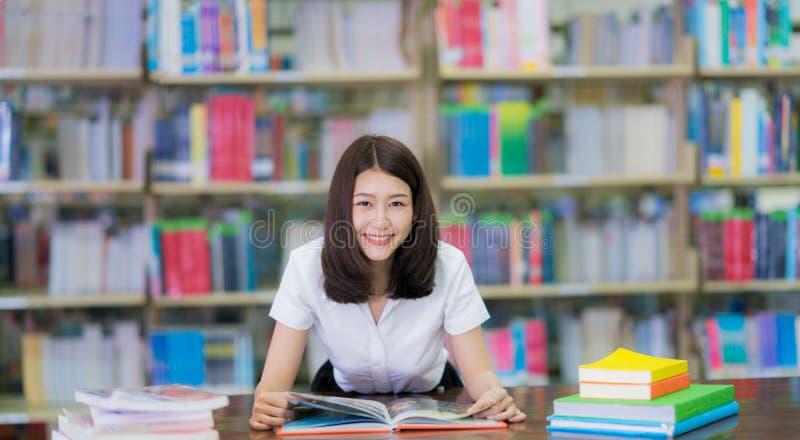 El estudiante asiático de la señora leyó un libro en biblioteca del campus en Universit fotos de archivo