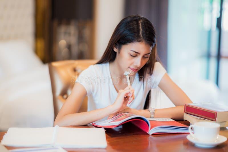 El estudiante asiático de la señora leyó un libro de texto para se prepara al examen o imágenes de archivo libres de regalías
