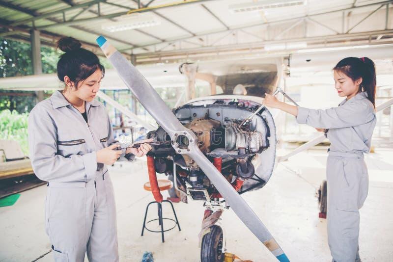 El estudiante asiático Engineers y los técnicos están reparando los aviones o fotografía de archivo