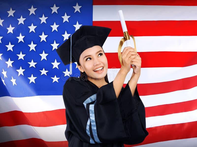 El estudiante asiático femenino feliz con los E.E.U.U. señala el fondo por medio de una bandera fotografía de archivo