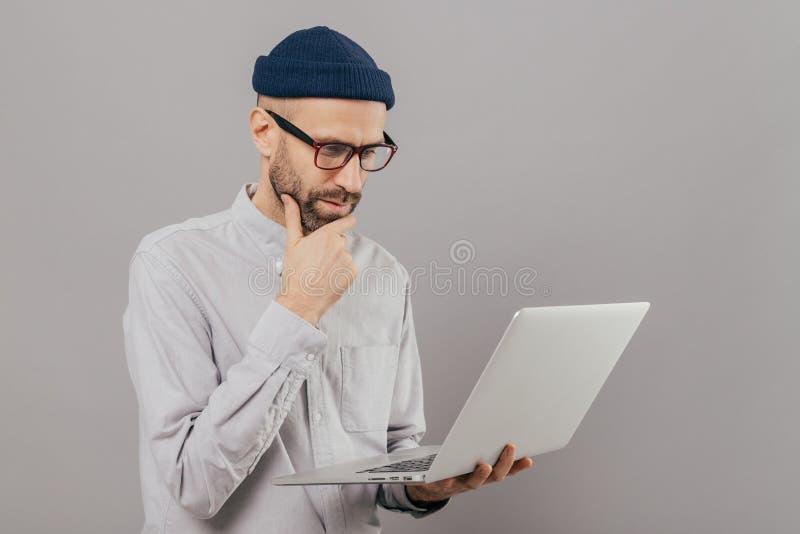 El estudiante atento sostiene la barbilla, enfocada en el monitor del ordenador portátil, busca la información para el proyecto,  foto de archivo libre de regalías