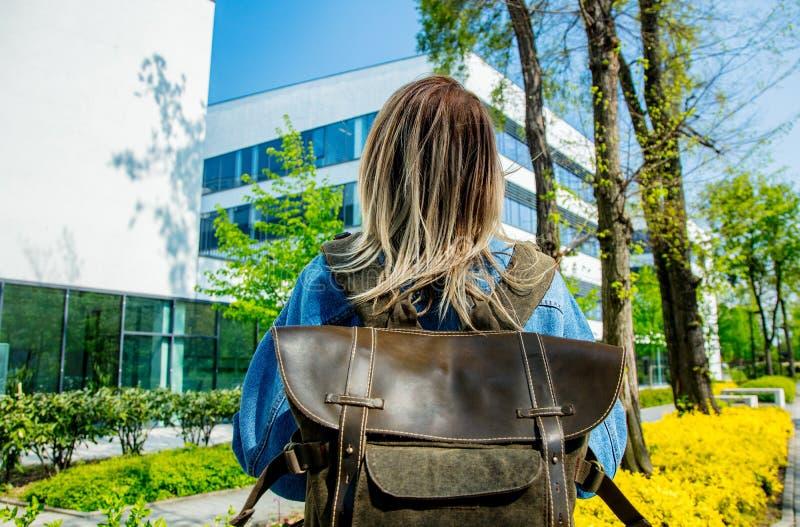 El estudiante con una mochila est? la primera vez cerca del campus de la universidad imagen de archivo libre de regalías