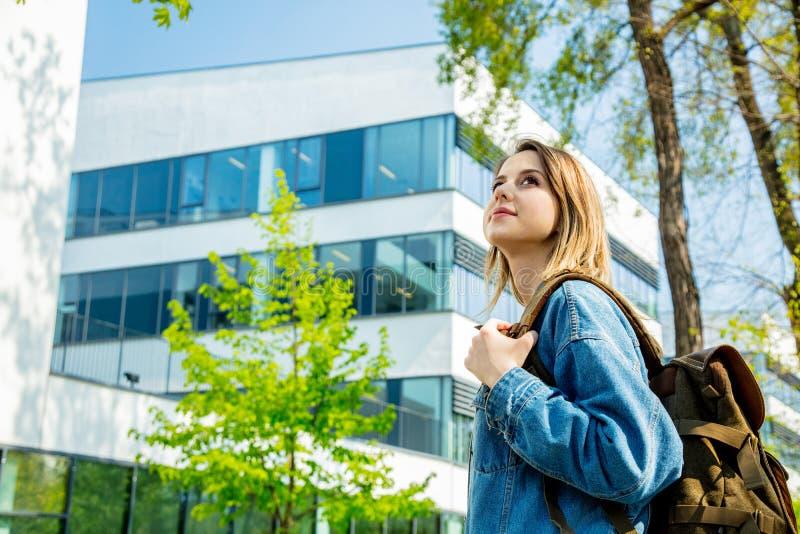 El estudiante con una mochila est? la primera vez cerca del campus de la universidad imágenes de archivo libres de regalías