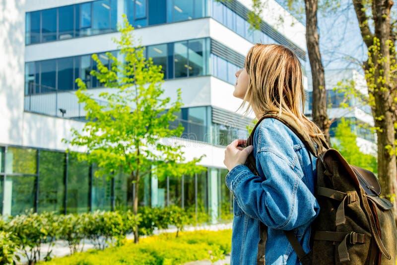 El estudiante con una mochila est? la primera vez cerca del campus de la universidad foto de archivo