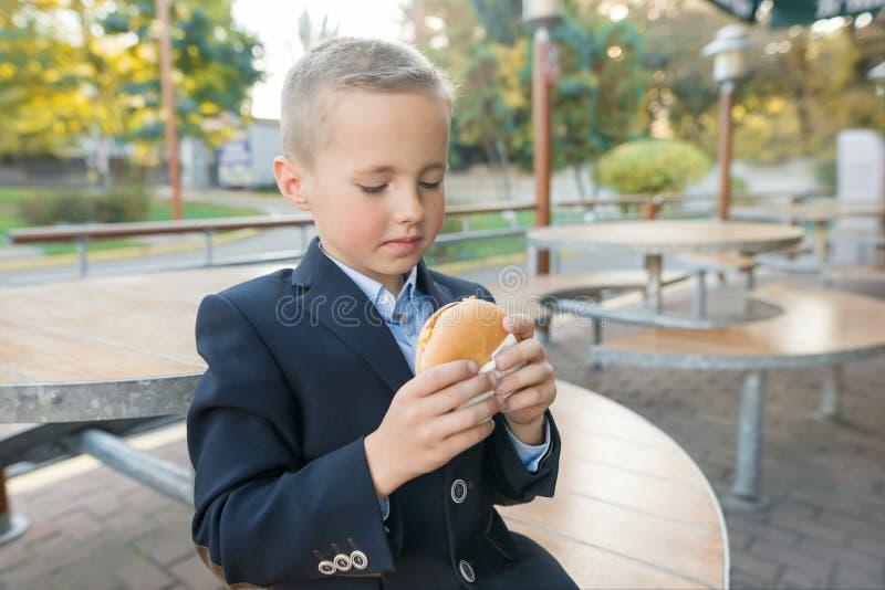 El estudiante de la escuela primaria del muchacho come la hamburguesa, bocadillo en un café al aire libre fotos de archivo libres de regalías