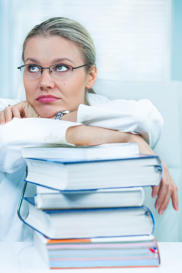 El estudiante de medicina femenino bastante joven está cansado de estudiar imagenes de archivo