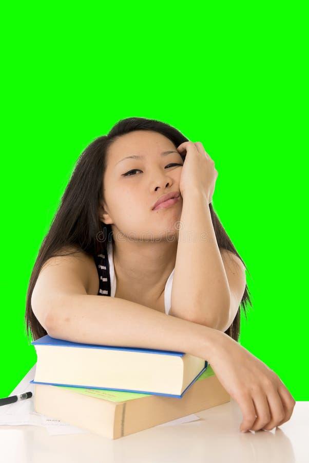 El estudiante de mujer bastante asiático trabajó demasiado en su ordenador portátil en el CCB blanco imagenes de archivo