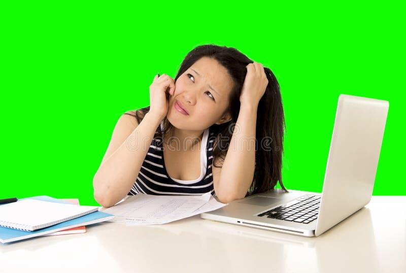 El estudiante de mujer bastante asiático trabajó demasiado en su ordenador portátil en llave verde del croma de la pantalla fotografía de archivo libre de regalías