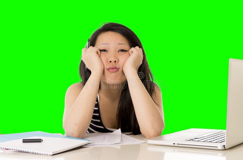 El estudiante de mujer bastante asiático trabajó demasiado en su ordenador portátil en llave verde del croma de la pantalla foto de archivo