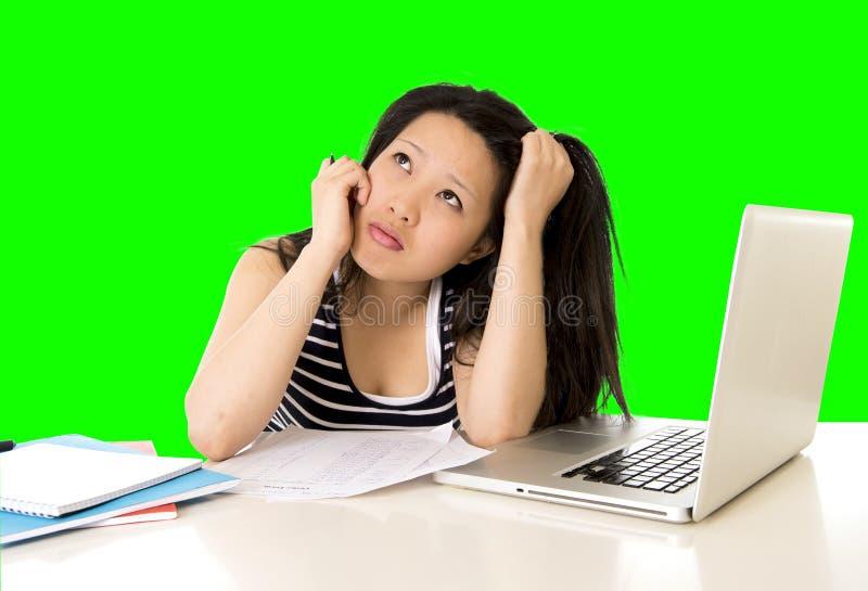 El estudiante de mujer bastante asiático trabajó demasiado en su ordenador portátil en llave verde del croma de la pantalla foto de archivo libre de regalías