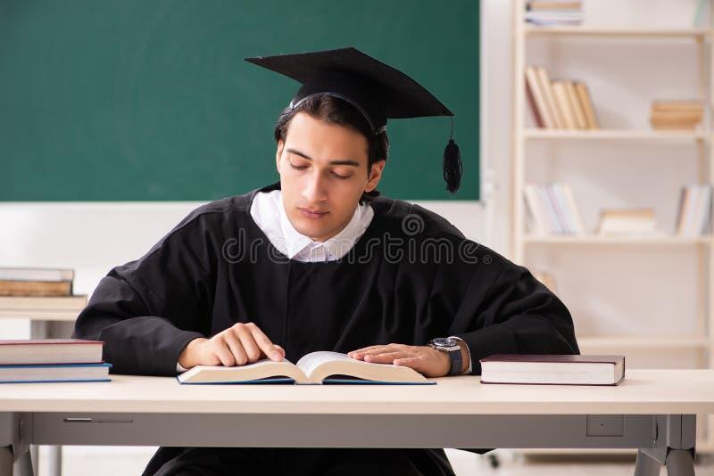 El estudiante de tercer ciclo delante del tablero verde fotografía de archivo