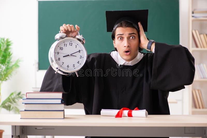 El estudiante de tercer ciclo delante del tablero verde fotos de archivo libres de regalías